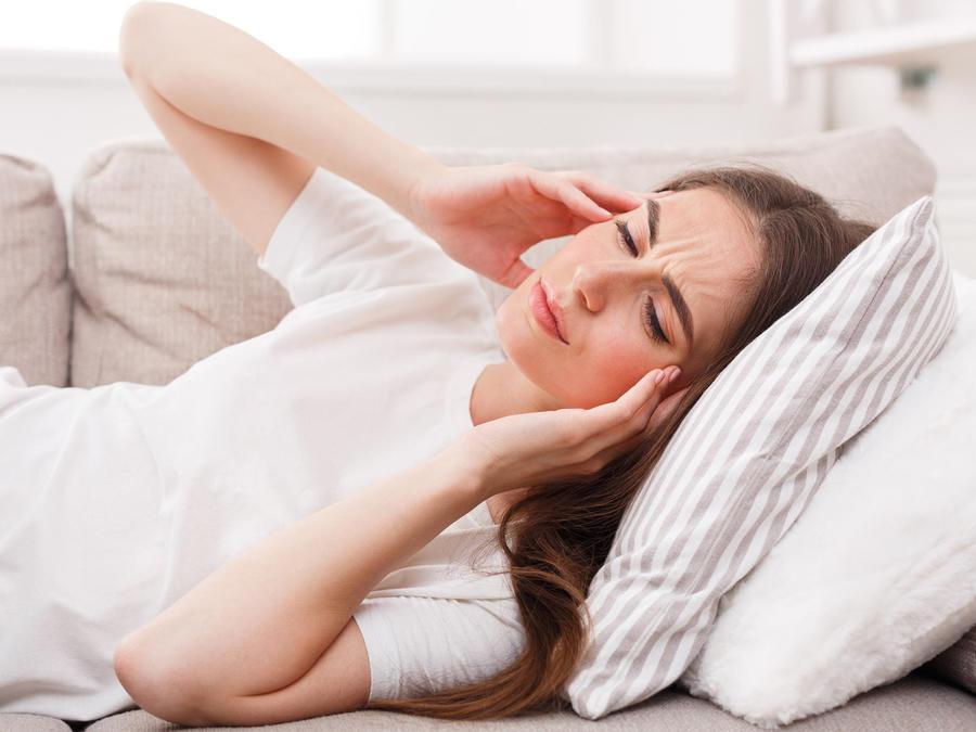 Mujer sintiéndose mal en el sofá