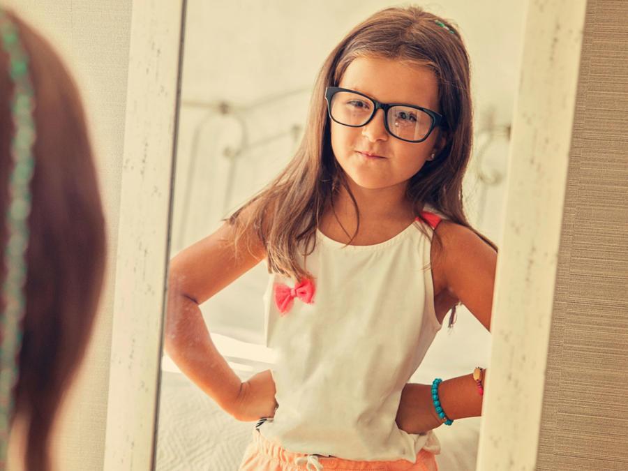 Niña con gafas mirándose al espejo