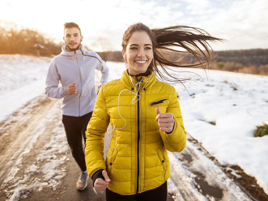 Pareja corriendo al aire libre en invierno