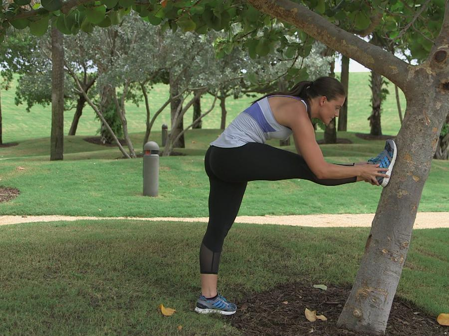 Gym trainer stretch in a tree of a park