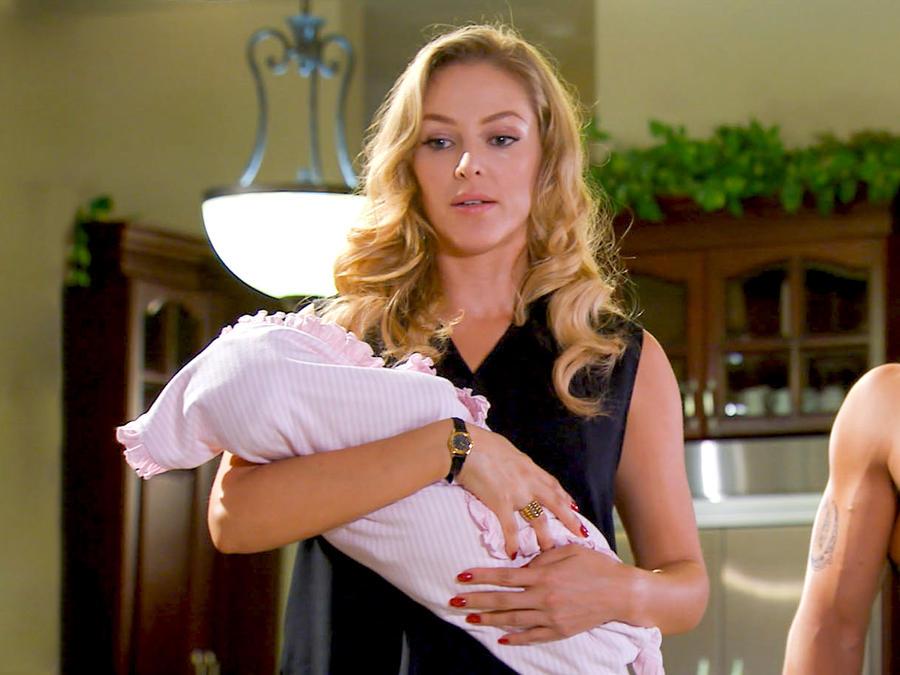 Erika de la Rosa cargando a una bebé en Bajo El Mismo Cielo