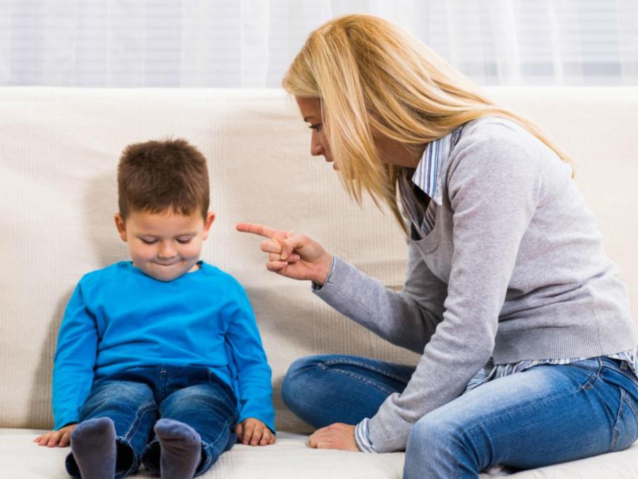 Mamá regañando a su hijo en un sillón