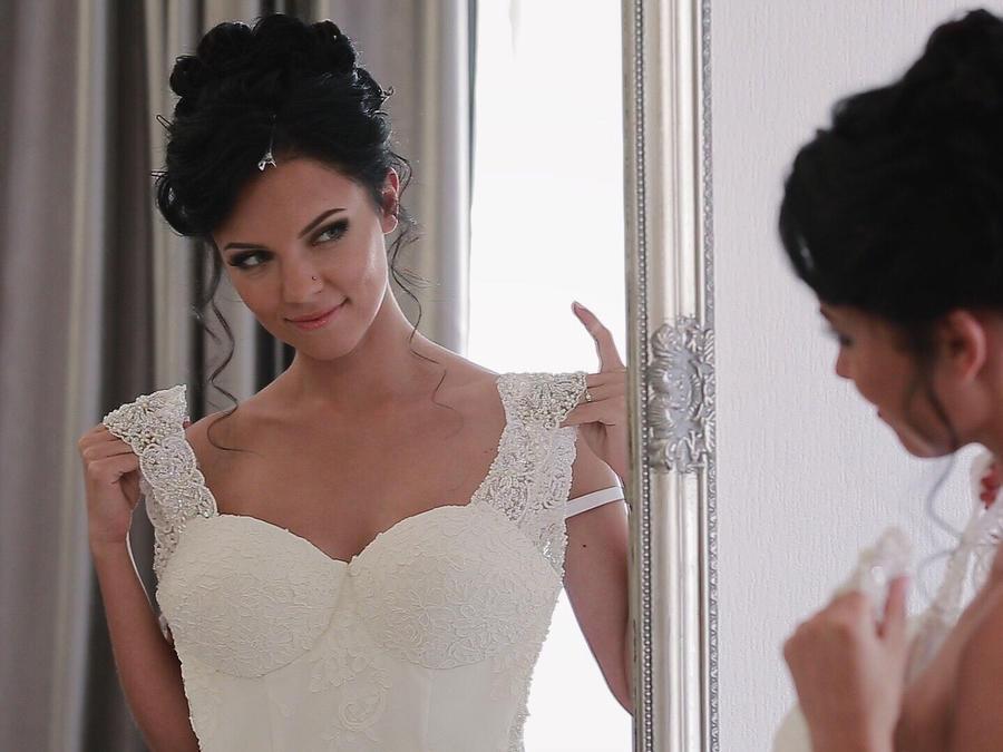 Mujer mirándose al espejo con su vestido de novia