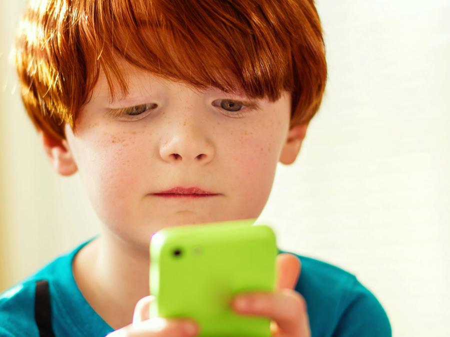 Niño pelirrojo jugando con un celular