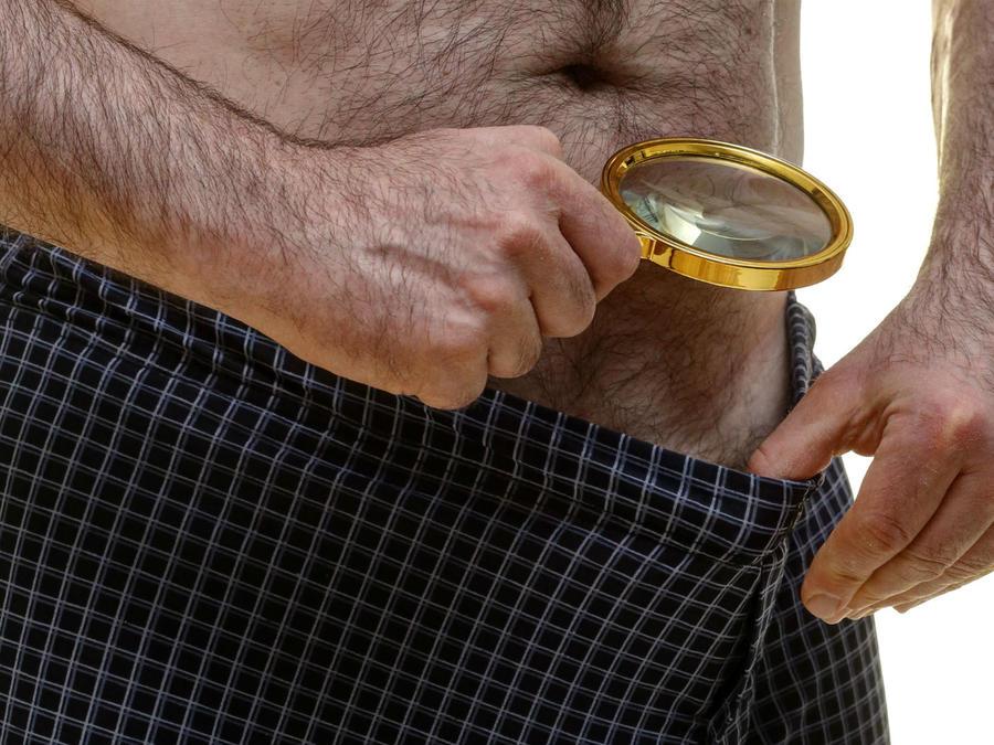 Hombre mirando sus genitales con una lupa