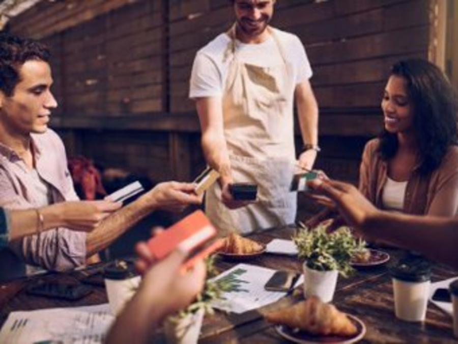 Clientes pagando con tarjeta de crédito en restaurante
