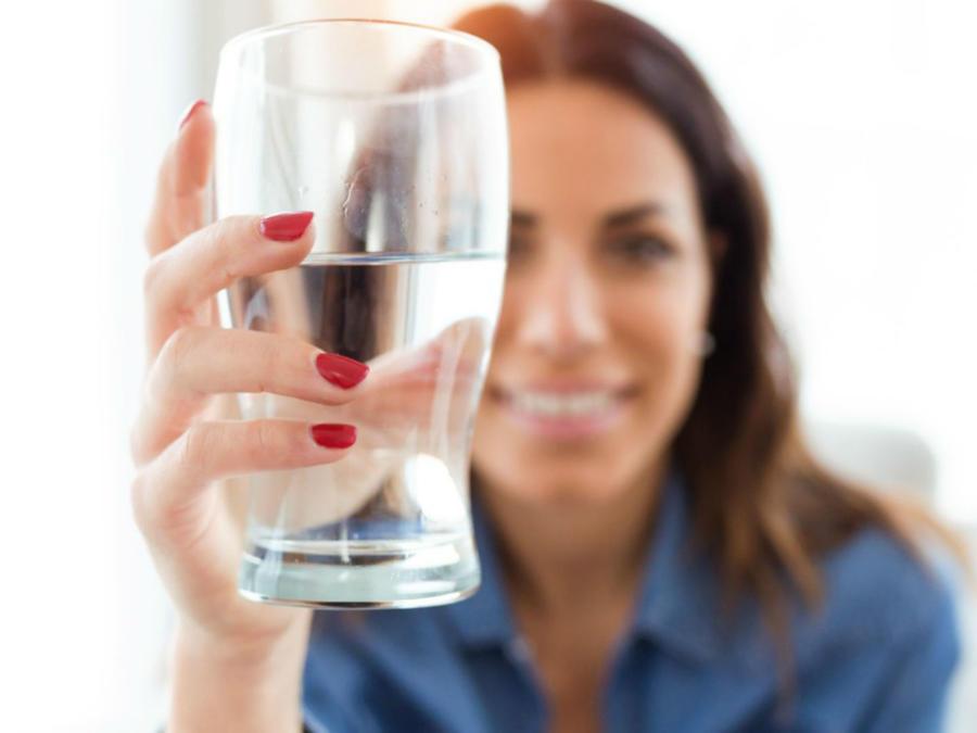 Mujer sosteniendo un vaso de agua