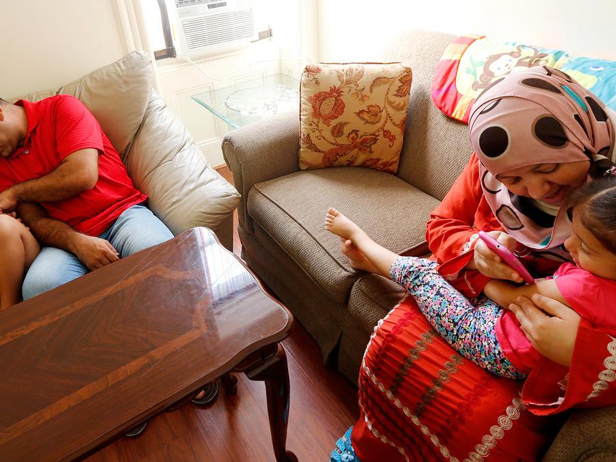 Suha carga a su hija de 3 años, Maaesa, mientras el papá Hussam juega con su hijo Wesam en su departamento en Jersey City, New Jersey, EEUU, el 16 de septiembre de 2015. La familia Alroustom huyó de Siria y logró rehacer su vida en EEUU.