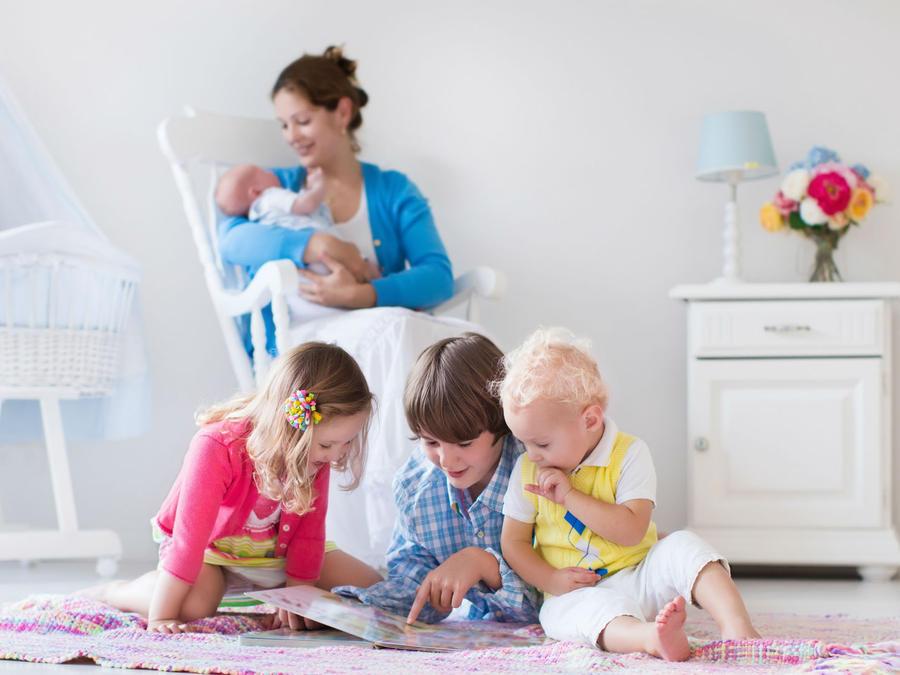 mamá con bebé en brazos junto a otros niños
