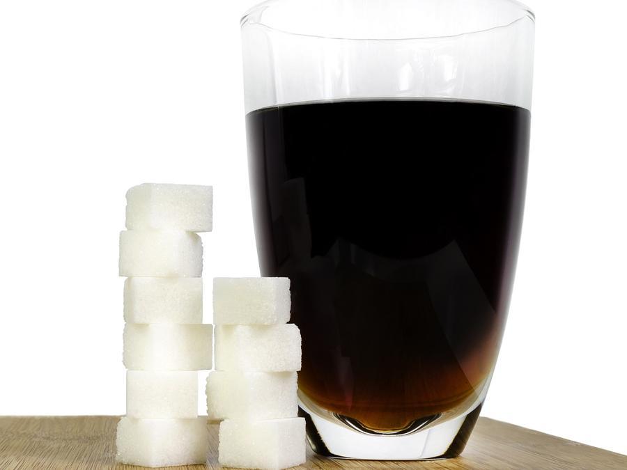 vaso de refresco de cola con cubos de azúcar al lado