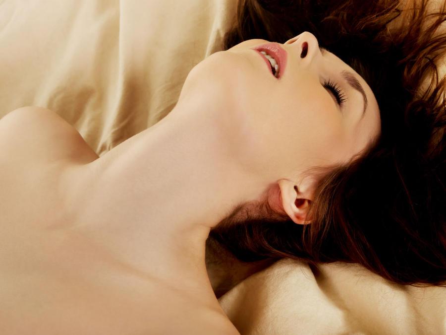 mujer desnuda sobre sábanas color arena
