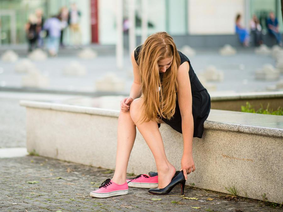 mujer cambiándose tacones por zapatillas rosas