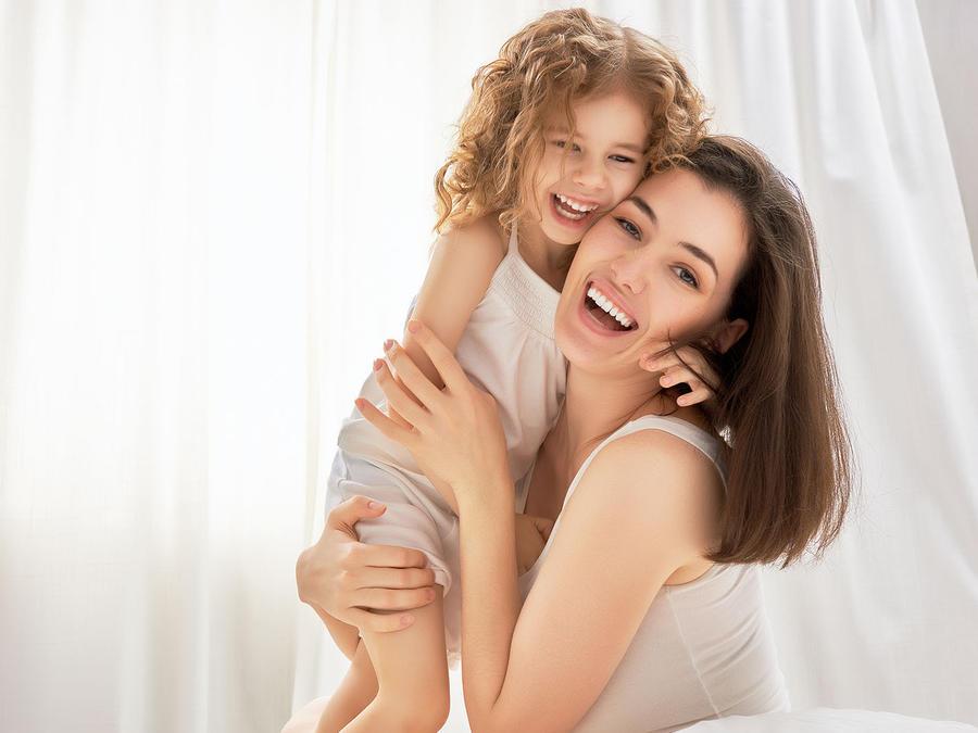madre e hija riendo abrazadas frente a una cortina blanca