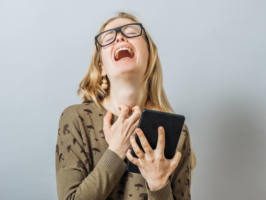 Mujer rubia con anteojos llorando con una tablet