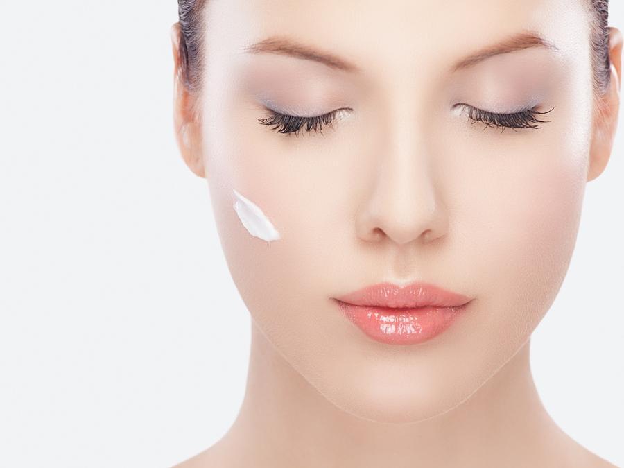 Mujer joven con los ojos cerrados con crema facial