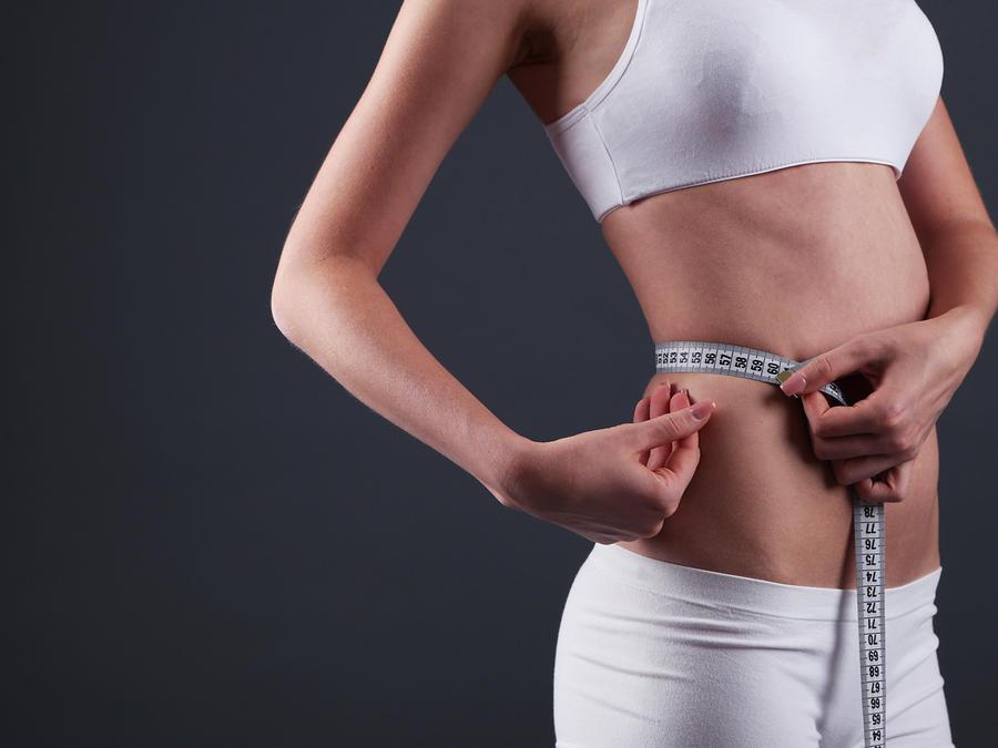Mujer midiendo su cintura sobre fondo negro