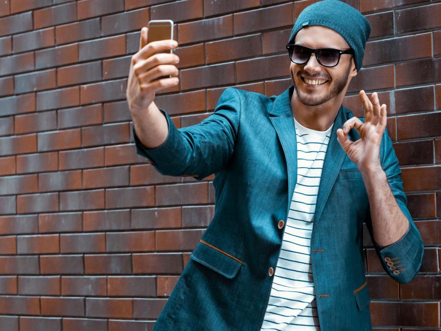 Hombre con lentes oscuros tomándose una selfie