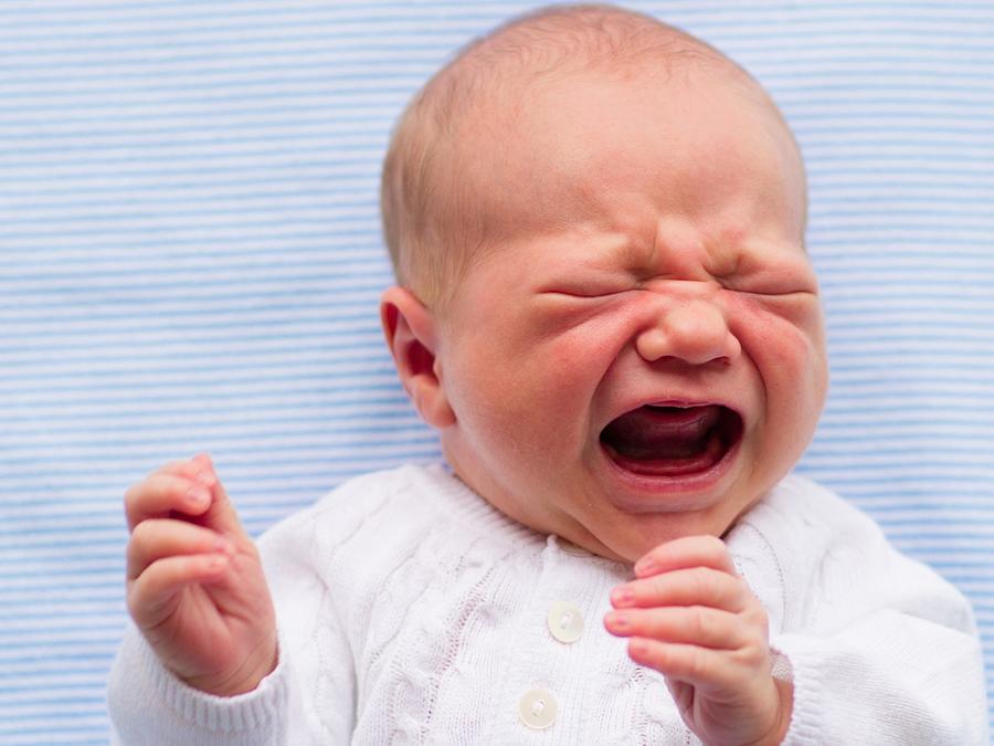 Bebé llorando sobre una sábana azul y blanca