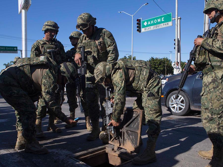 """Efectivos de la Marina mexicana revisan una alcantarilla donde se hallaron armas de alto poder abandonadas en un barrio de Los Mochis, México, donde fuerzas especiales locazaron a Joaquín """"El Chapo"""" Guzmán, el sábado 9 de enero de 2016"""