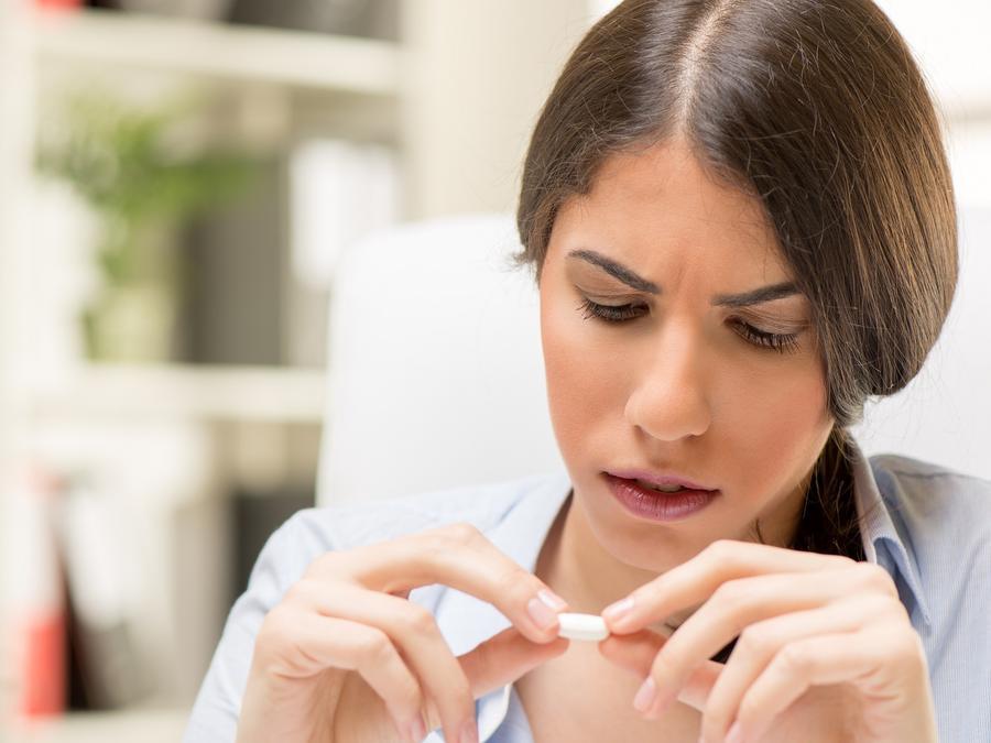 Mujer con blusa azul sosteniendo una píldora y analizándola