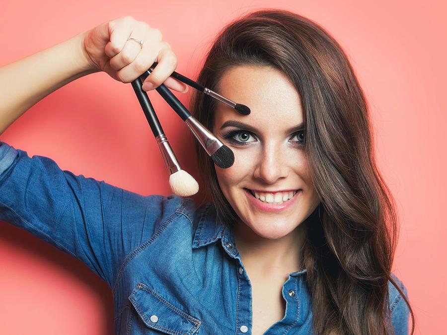 Mujer de cabello marrón sosteniendo pinceles de maquillaje
