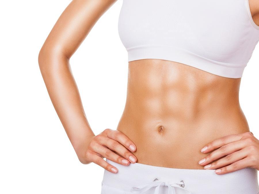 Mujer con ropa deportiva blanca mostrando sus abdominales
