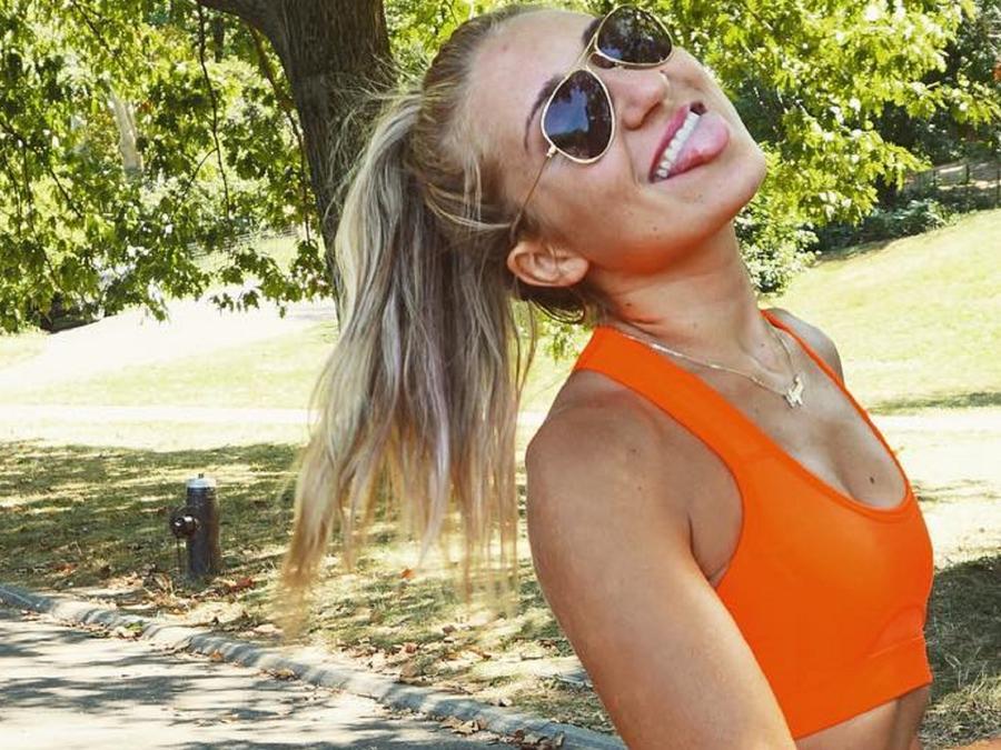 Alyssa Bossio con equipo deportivo naranja y lentes oscuros