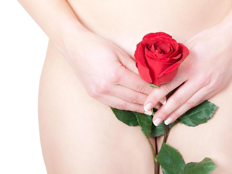 Mujer sosteniendo una rosa frente a su vagina