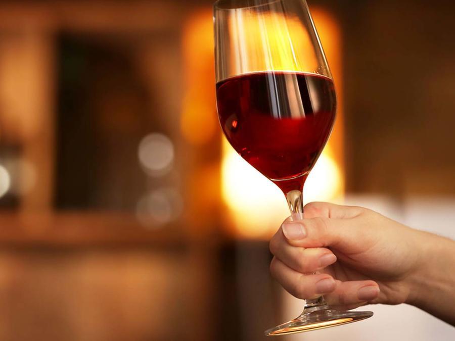 Mano femenina sostiene copa de vino tinto