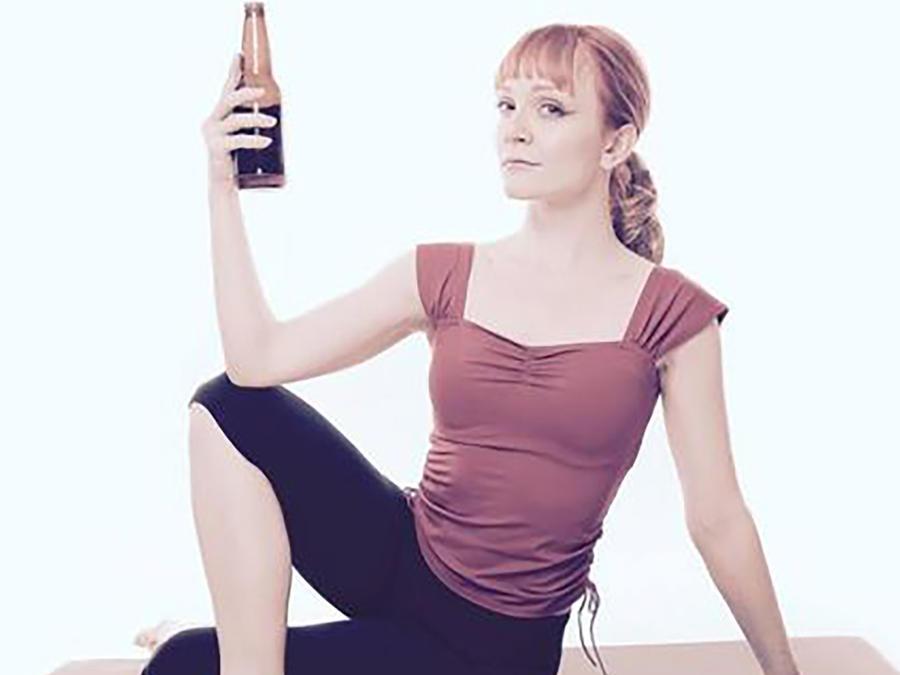 Mujer en pose de yoga sosteniendo una cerveza