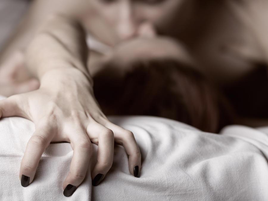 Pareja en la cama teniendo relaciones sexuales