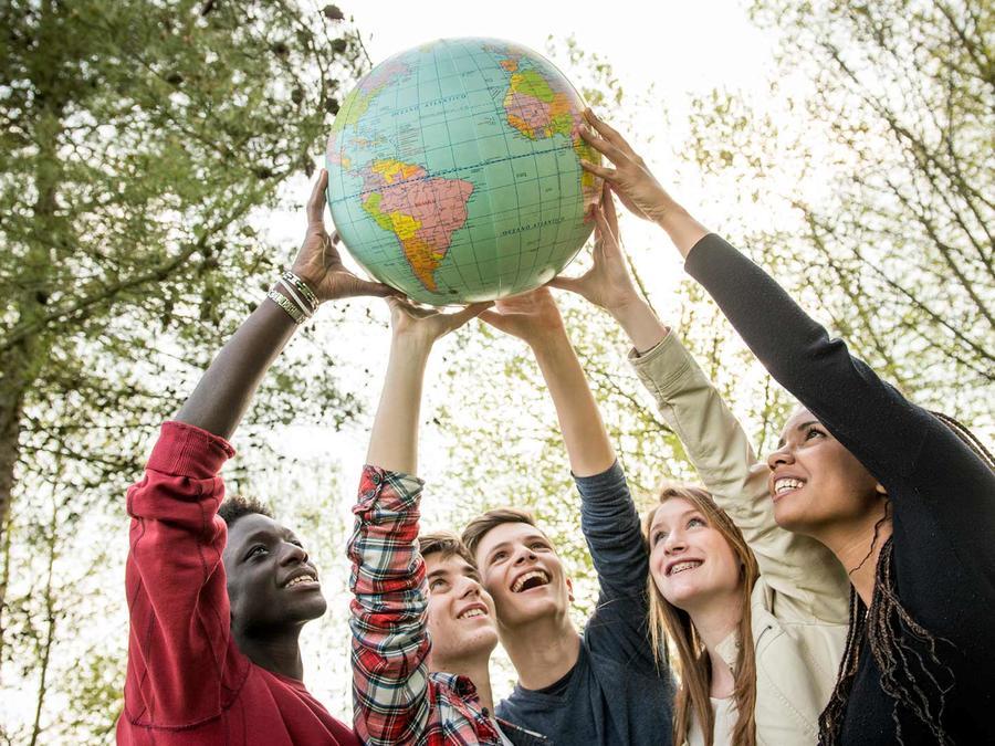 Teenagers levantando globo terráqueo en alto