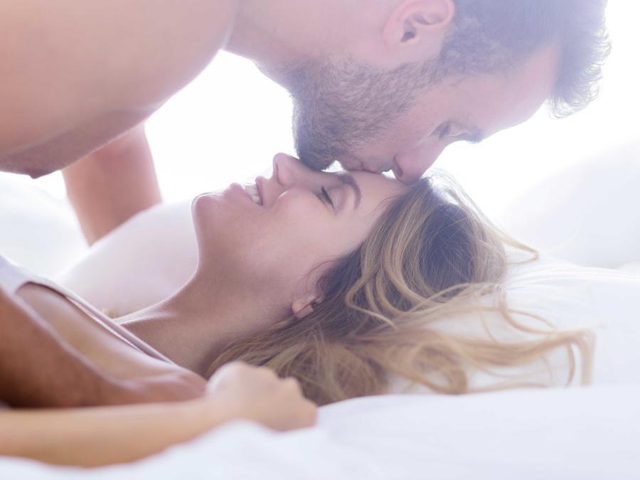 Hombre besando en la frente a su pareja en la cama