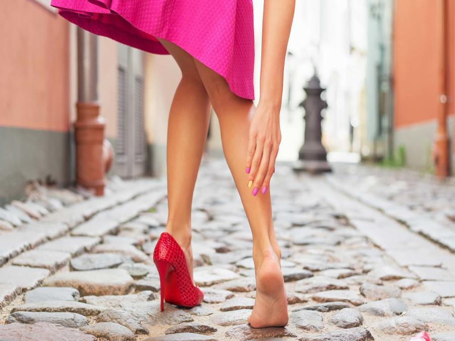 Mujer en la calle sin un tacón tocando su tobillo