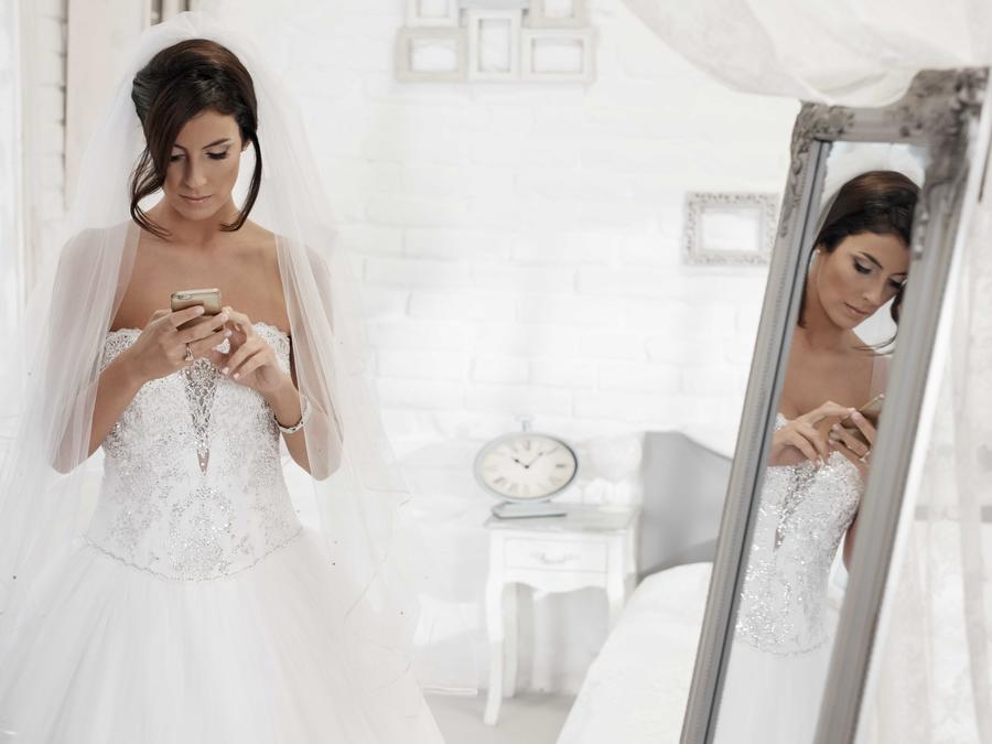 Novia revisando el celular frente al espejo