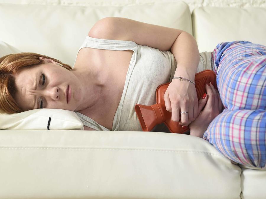 Mujer acostada en el sofá con compresa caliente en el vientre