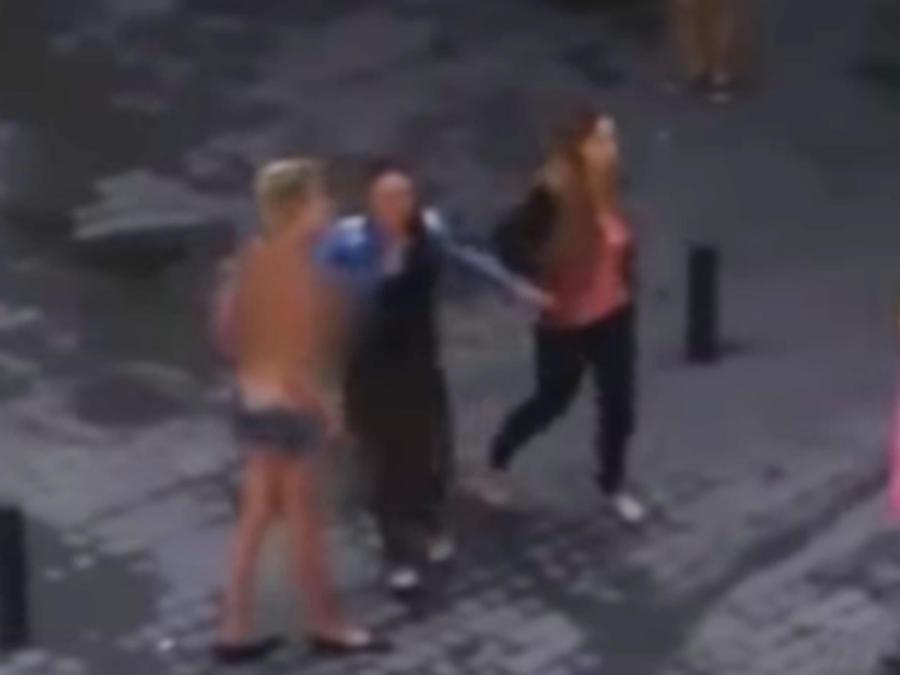 Con los pechos al aire un grupo de prostitutas se enfrenta en medio de la calle