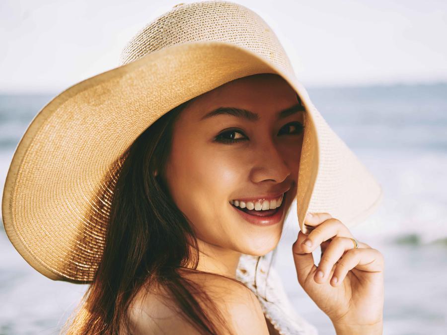Mujer asiática con sombrero en el mar