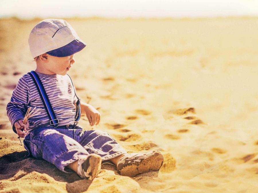 Bebé sentado en la arena bajo el sol