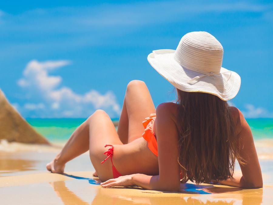 Mujer tomando sol tumbada sobre la arena