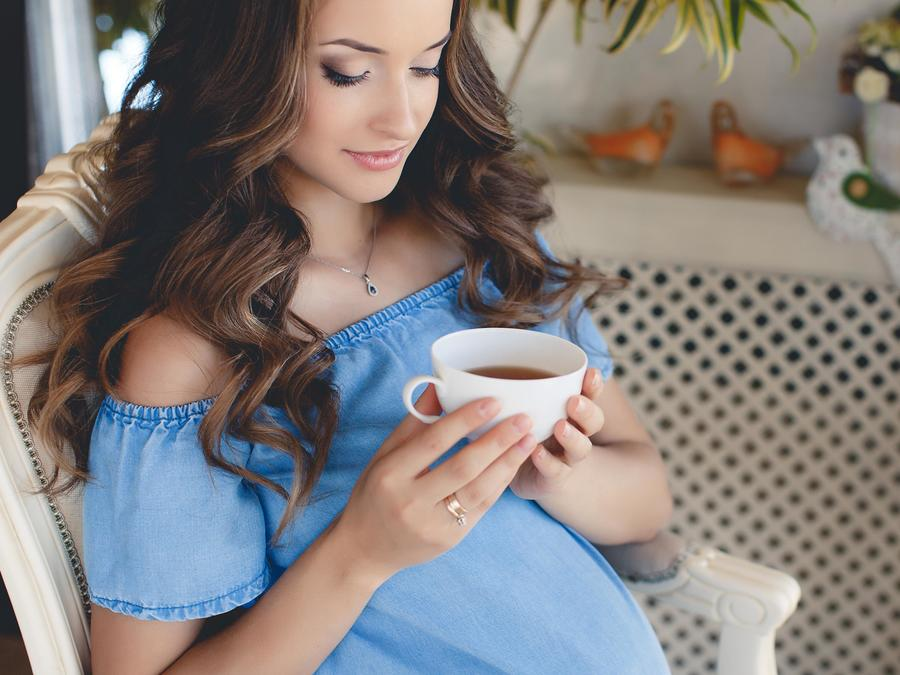 Mujer embarazada sosteniendo una taza de te