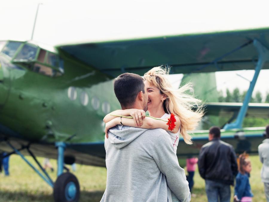 Pareja besándose al lado de un avión