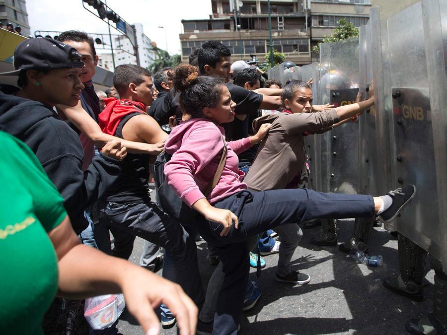 En esta imagen de archivo, tomada el 2 de junio de 2016, una mujer patea el escudo de un soldado de la Guarda Nacional mientras otros manifestantes empujan durante protestas por la comida