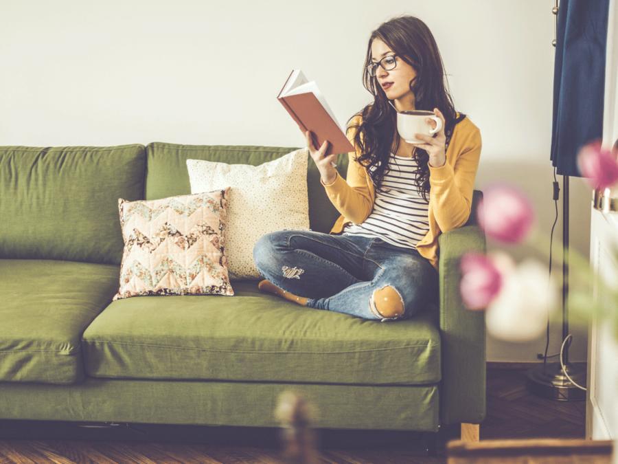 Mujer joven leyendo en el sofá con un café