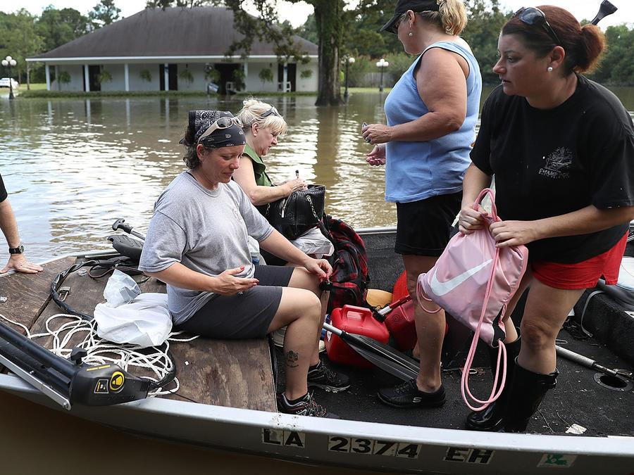 Residentes de Baton Rouge, Louisiana suben a una embarcación para dejar sus casas e ir en busca de suministros tras inundaciones históricas en el estado