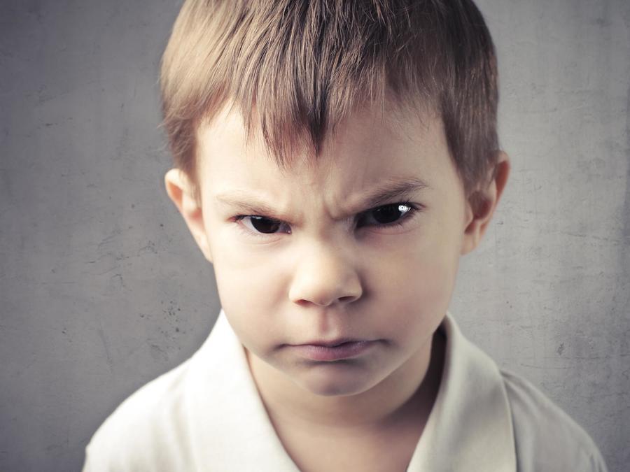 Niño mal humorado con el ceño fruncido