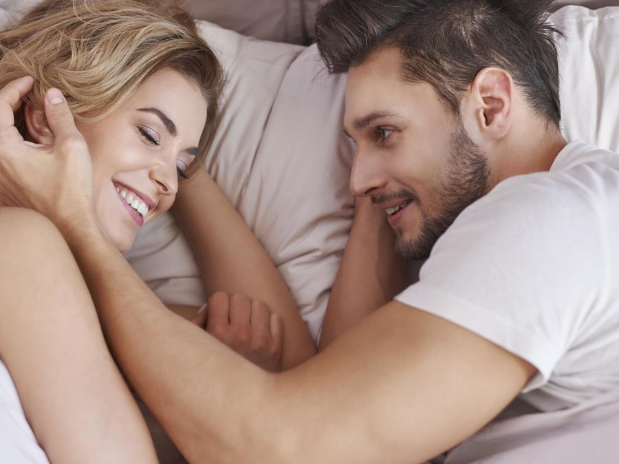 Pareja sonriendo acostados en una cama
