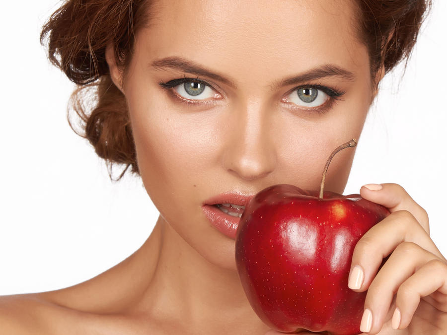 Mujer sosteniendo una manzana roja