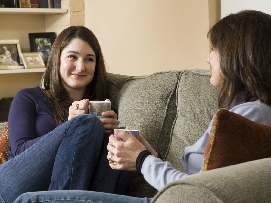 Madre e hija adolescente en el sofá compartiendo una taza de café y sonriendoMadre e hija adolescente en el sofá compartiendo una taza de café y sonriendo