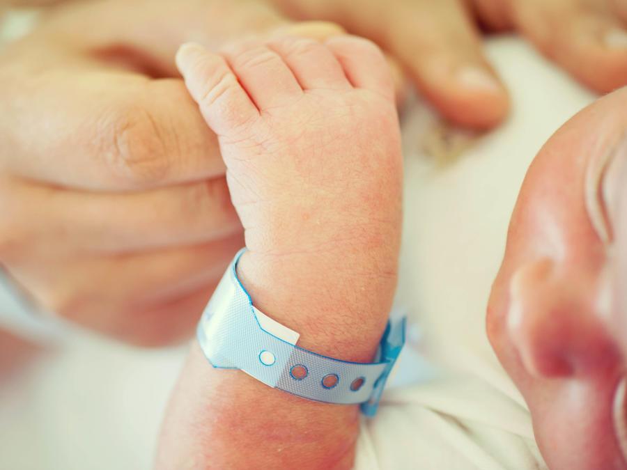 Recién nacido agarrado de la mano de su papá